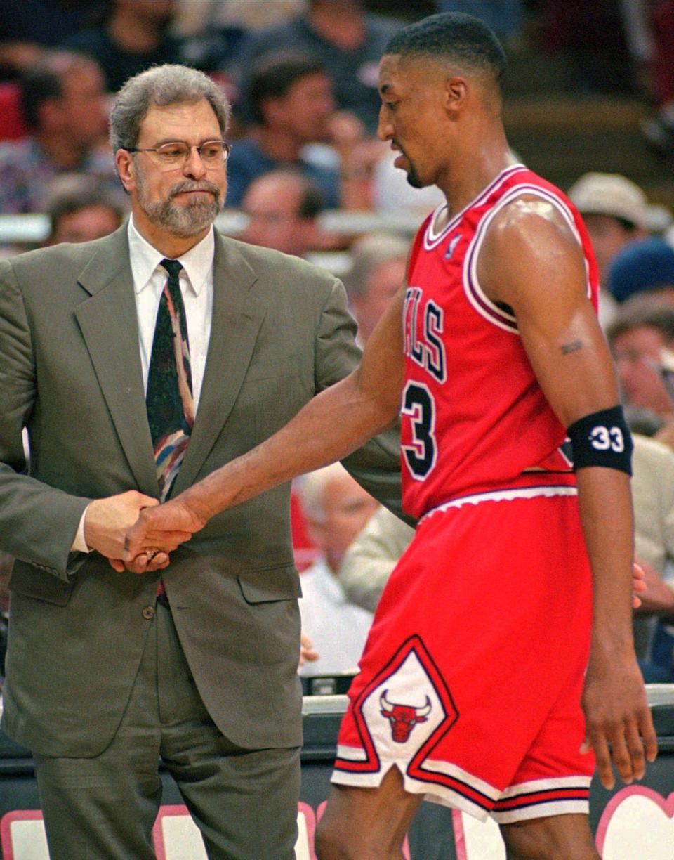 Former Chicago Bulls head coach Phil Jackson, left, shakes hands with former Bulls star Scottie Pippen during a May 25, 1996 playoff game.
