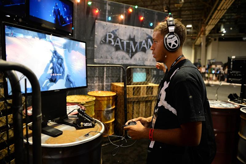 """FILE - In this Aug. 28, 2013 file photo, an attendee plays """"Batman: Arkham Origins"""" at GameStop Vegas 2013, in Las Vegas. The developers of the upcoming video game are taking the superhero back to basics for the third installment in Warner Bros. Interactive Entertainment's popular """"Arkham"""" series, primed for release Oct. 25, 2013. (Photo by Al Powers/Invision/AP, File)"""