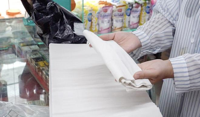 A shopowner in Sikai shows how girls fashion cheap paper into rough sanitary pads. Photo: Handout