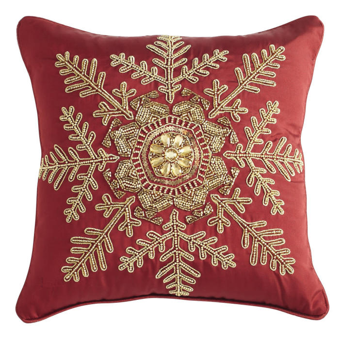 In this photo provided by Pier 1 Imports, gold beading and the deep hue of this snowflake-emblazoned pillow from Pier1.com reference two big holiday themes; metallics and crimson red. Following the general trend in home decor, holiday trim and accessories this year are a mix of eclectic and traditional colors and styles. Style watchers say we're approaching the holidays with a more open mind, and decor has never been more expansive in terms of what works. (AP Photo/Pier 1 Imports)