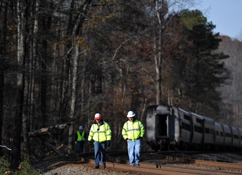 Workers walk on the tracks after the Amtrak Crescent train derailed, Monday, Nov. 25, 2013, in Spartanburg County, S.C. Several cars of the New York City-bound train with 218 people aboard went off the tracks early Monday as bags flew and jolted passengers clung to each other, authorities and passengers said. There were no serious injuries. (AP Photo/Rainier Ehrhardt)