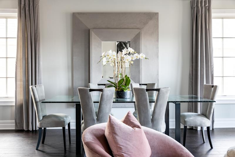 In the dining room, gray suede covers chairs by Korban with a V-shaped back detail.