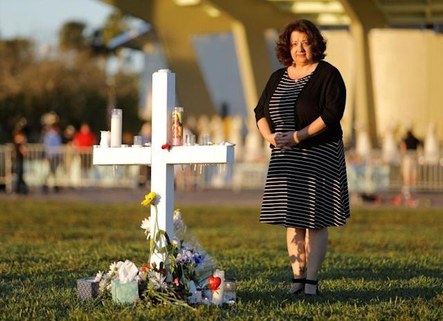 Diana Haneski stands next to a cross erected for the victims of the school shooting in Parkland, Florida: REUTERS