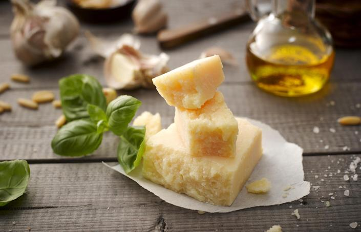 Three chunks of Parmesan in a stack with basil, pine nuts, garlic, coarse salt, and a small bottle of oil in the background