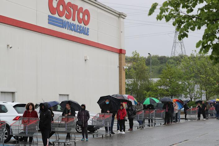 People queue outside Costco in Thurrock, Essex, during a minutes silence paying tribute to the NHS staff and key workers who have died during the coronavirus outbreak. (Photo by Gareth Fuller/PA Images via Getty Images)