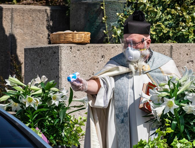 Father Pelc sprayed holy water to churchgoers using a squirt gun on Easter weekend. / Credit: Larry Peplin