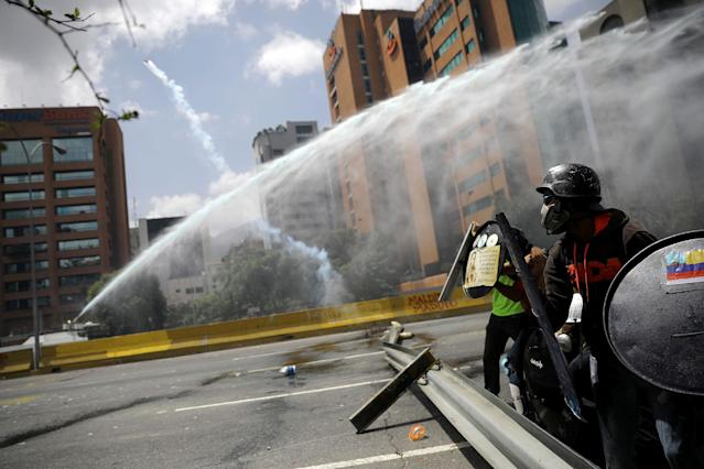 <p>A jet of water is aimed at demonstrators during a rally against Venezuela's President Nicolas Maduro in Caracas, Venezuela, May 26, 2017. (Carlos Barria/Reuters) </p>