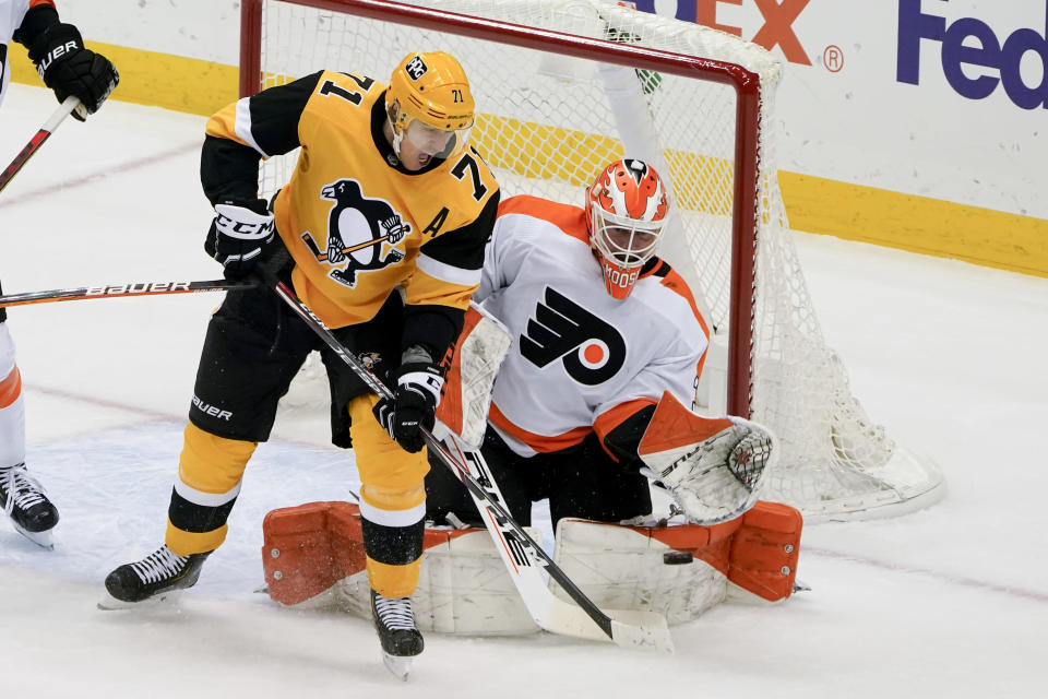 Philadelphia Flyers goaltender Brian Elliott (37) makes a save as Pittsburgh Penguins' Evgeni Malkin (71) looks for a rebound during the first period of an NHL hockey game Thursday, March 4, 2021, in Pittsburgh. (AP Photo/Keith Srakocic)