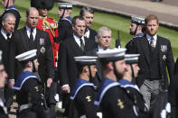 The Earl of Snowdon, Britain's Prince William, Peter Phillips, Vice Admiral Sir Timothy Laurence, Prince Andrew and Prince Harry, from left, follow the coffin as it slowly makes its way in a ceremonial procession during the funeral of Britain's Prince Philip inside Windsor Castle in Windsor, England, Saturday, April 17, 2021. (Gareth Fuller/Pool via AP)