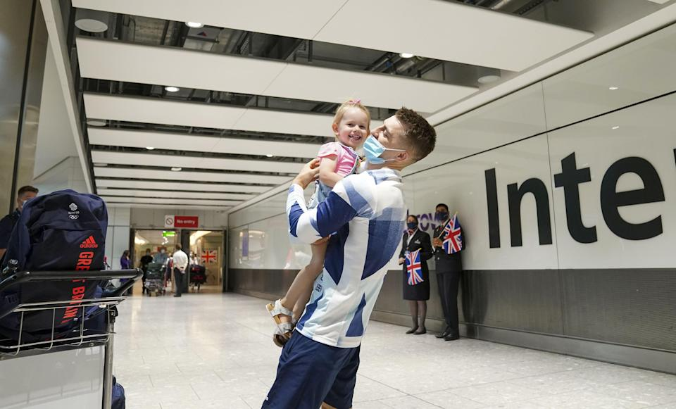 Olympic gymnast Max Whitlock hugs his daughter Willow as he arrives back at London Heathrow Airport (Steve Parsons/PA) (PA Wire)