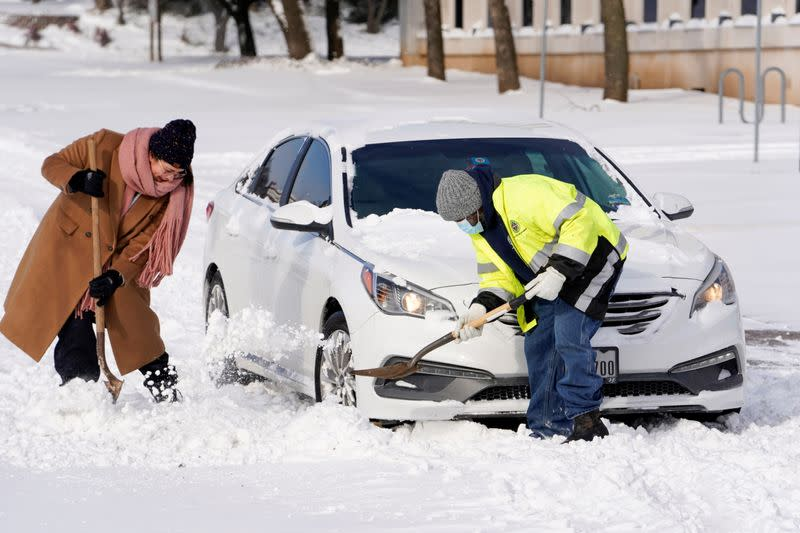 Quincy Perkins helps a woman free her stuck vehicle during record breaking cold weather in Oklahoma City