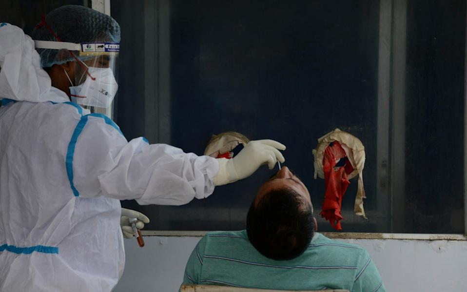A health worker collects nasal swab for a Covid-19 coronavirus RT PCR test at the North Bengal Medical College and Hospital on the outskirts of Siliguri - DIPTENDU DUTTA / AFP