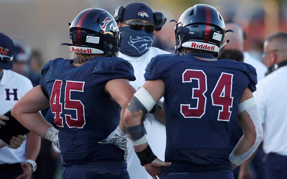 A Herriman Mustangs masked coach talks to his players during a game against the Davis Darts - GEORGE FREY/REUTERS