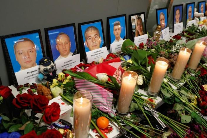 Flowers and candles are placed in front of the portraits of the flight crew members of the Ukraine International Airlines Boeing 737-800 plane that crashed in Iran, at a memorial at Boryspil International airport