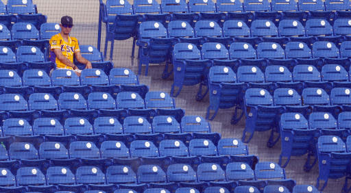 An LSU fans sits in the rain watching Georgia play Mississippi during the seventh inning of a Southeastern Conference tournament NCAA college baseball game, Thursday, May 24, 2018, in Hoover, Ala. (AP Photo/Butch Dill)