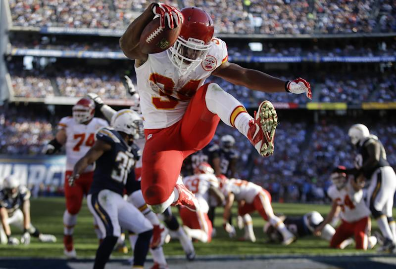 Kansas City Chiefs running back Knile Davis, center, jumps in the end zone as he scores a touchdown against the San Diego Chargers during the first half of an NFL football game, Sunday, Dec. 29, 2013, in San Diego. (AP Photo/Lenny Ignelzi)