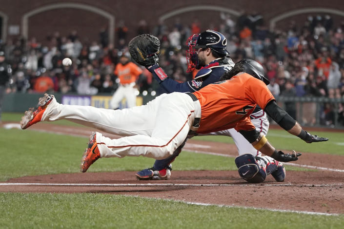 San Francisco Giants' Brandon Crawford, foreground, slides into home to score the winning run past Atlanta Braves catcher Travis d'Arnaud during the 11th inning of a baseball game in San Francisco, on Friday, Sept. 17, 2021. (AP Photo/Jeff Chiu)