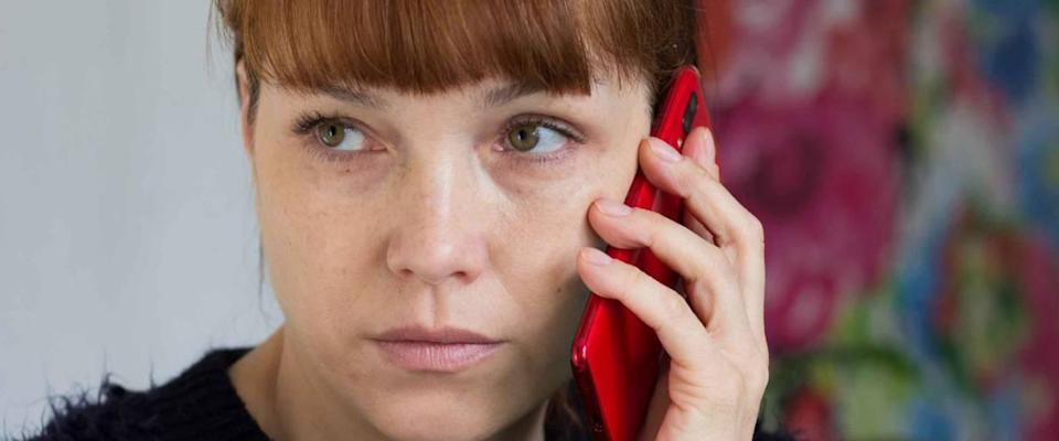 Portrait of serious middle aged woman holding mobile phone and looking aside