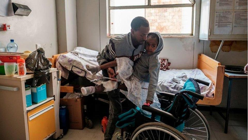 Arsema Berha, 9-years-old, is moved into her bed by a relative at Ayder Referral Hospital in the Tigray capital Mekele on February 25, 2021, after being injured during fighting between the Tigray People's Liberation Front (TPLF) which fell after Ethiopian Prime Minister deployed troops and warplanes to oust the TPLF late last year