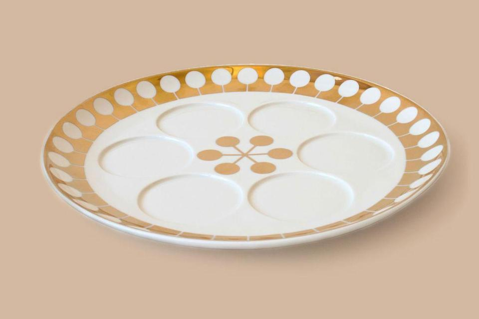 """<p>For a posh look, designer Jonathan Adler serves up this piece from his latest collection—the golden accents give this porcelain Seder plate an elegant finish for any modern table at Passover. </p> <p><em><strong>Shop Now:</strong> Jonathan Adler """"Futura"""" Seder Plate, $150, <a href=""""https://jonathanadler.com/products/futura-seder-plate?variant_id=31498352295970"""" rel=""""nofollow noopener"""" target=""""_blank"""" data-ylk=""""slk:jonathanadler.com"""" class=""""link rapid-noclick-resp"""">jonathanadler.com</a>. </em></p>"""