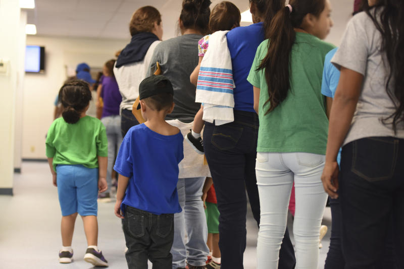 Mothers and their children stand in line at South Texas Family Residential Center