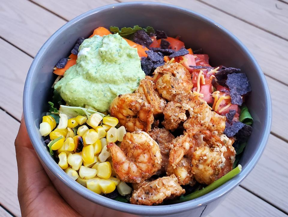 hand holding bowl of salad with greens, corn, shrimp, and green dressing