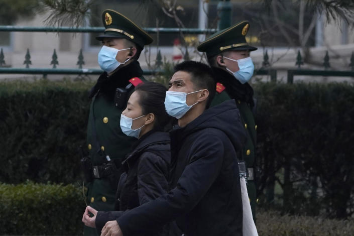 Residents wearing masks past by paramilitary officers on duty near the Great Hall of the People where delegates are attending the opening session of the Chinese People's Political Consultative Conference (CPPCC) held in Beijing on Thursday, March 4, 2021. (AP Photo/Ng Han Guan)