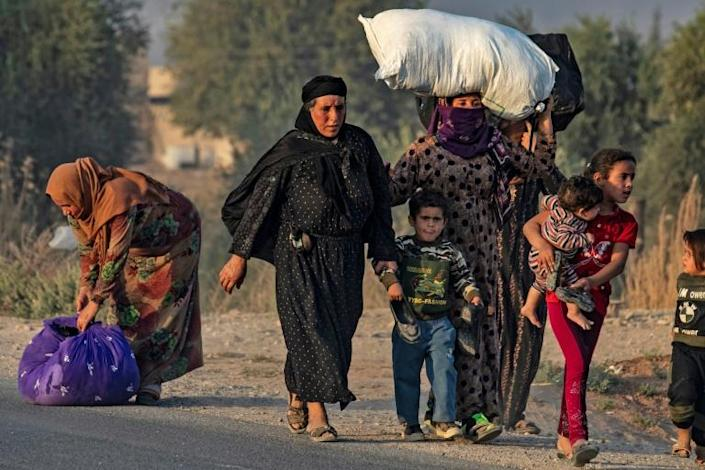 Civilians flee amid Turkish bombardment on Syria's northeastern town of Ras al-Ain in the Hasakeh province along the Turkish border on Wednesday (AFP Photo/Delil SOULEIMAN)