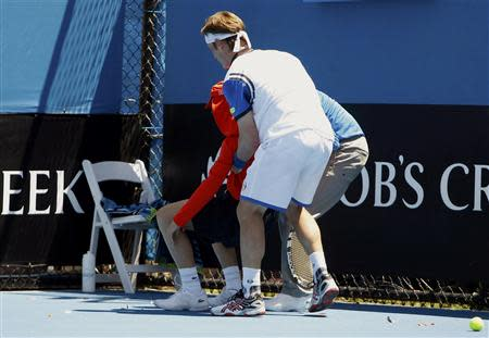 Daniel Gimeno-Traver (front) of Spain assists an official in helping a ball boy who collapsed during his men's singles match against Milos Raonic of Canada at the Australian Open 2014 tennis tournament in Melbourne January 14, 2014. REUTERS/Brandon Malone