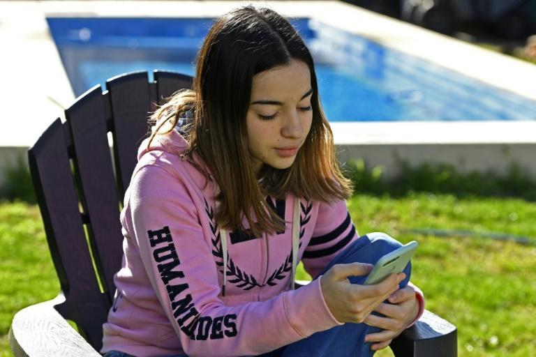 Argentine high school student Jazmin Islas uses her cell phone at her home's yard in La Plata, Buenos Aires, Argentina, on July 28, 2020