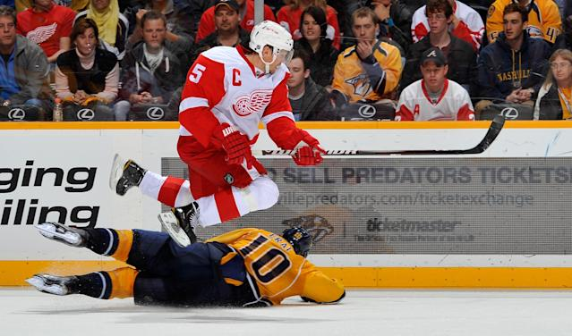 NASHVILLE, TN - DECEMBER 15: Nicklas Lidstrom #5 of the Detroit Red Wings jumps over Martin Erat #10 of the Nashville Predators at the Bridgestone Arena on December 15, 2011 in Nashville, Tennessee. (Photo by Frederick Breedon/Getty Images)