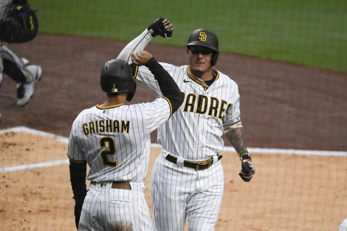 San Diego Padres' Manny Machado, right, is congratulated by Trent Grisham (2) after hitting a two-run home run during the first inning of a baseball game against the Colorado Rockies, Monday, May 17, 2021, in San Diego. (AP Photo/Denis Poroy)