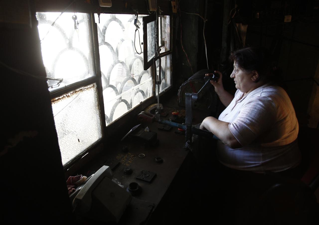 Eliza Kobiashvili, 56, operates 60-year-old cable cars from her booth in the town of Chiatura, some 220 km (136 miles) northwest of Tbilisi, September 12, 2013. Dating to the Soviet era, Chiatura's public cable cars were built to facilitate the manganese mining industry, which formed the bedrock of the town's economy. Sixty years later, 15 of Chiatura's 21 cable car routes are still running, covering a total length of over 6000 meters, and they are still the quickest and most convenient way of getting around, despite their advanced years. Picture taken September 12, 2013. REUTERS/David Mdzinarishvili (GEORGIA - Tags: SOCIETY TRANSPORT)  ATTENTION EDITORS: PICTURE 29 OF 31 FOR PACKAGE 'CHIATURA'S CRUMBLING CABLE CARS'.  SEARCH 'CHIATURA DAVID' FOR ALL IMAGES