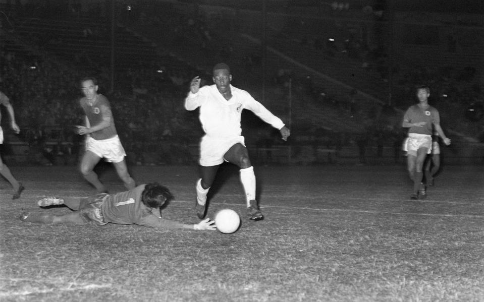 Hongkong's goalkeeper Chu Pak-wo dives at the feet of Pele, but Pele side-steps him and scores his second goal for the match. Hongkong vs Santos at the Hongkong Stadium. 10DEC70 SCMP/Chan Kiu (Photo by Chan Kiu/South China Morning Post via Getty Images)