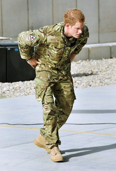 Britain's Prince Harry examines the 30mm cannon of an Apache helicopter Friday Sept 7 2012 at Camp Bastion in Afghanistan, where he will be operating from during his tour of duty as a co-pilot gunner. The Prince has returned to Afghanistan to fly attack helicopters in the fight against the Taliban. (AP Photo/ John Stillwell, Pool)