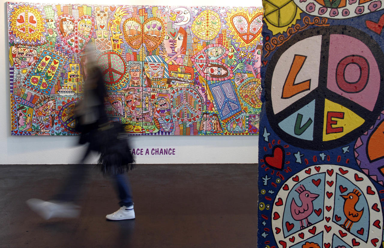 """A woman walks alongside the painting """"Give peace a Chance"""" by James Rizzi during the opening of his exhibition """"Rizzi's World - 60 Years of James Rizzi"""" in Bremen, northern Germany, on Thursday, May 20, 2010. The exhibtion shows about 1,200 of Rizzi's works.  (apn Photo/Focke Strangmann)"""