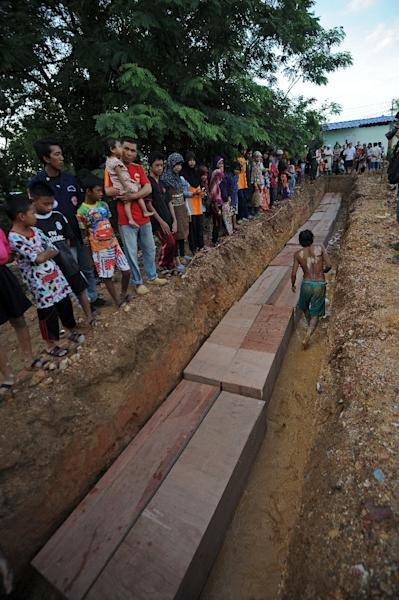 Residents watch as coffins containing the remains of migrants exhumed from a mass grave at an abandoned jungle camp in the Sadao district of Thailand's southern Songkhla province bordering Malaysia on May 3, 2015 (AFP Photo/Madaree Tohlala)