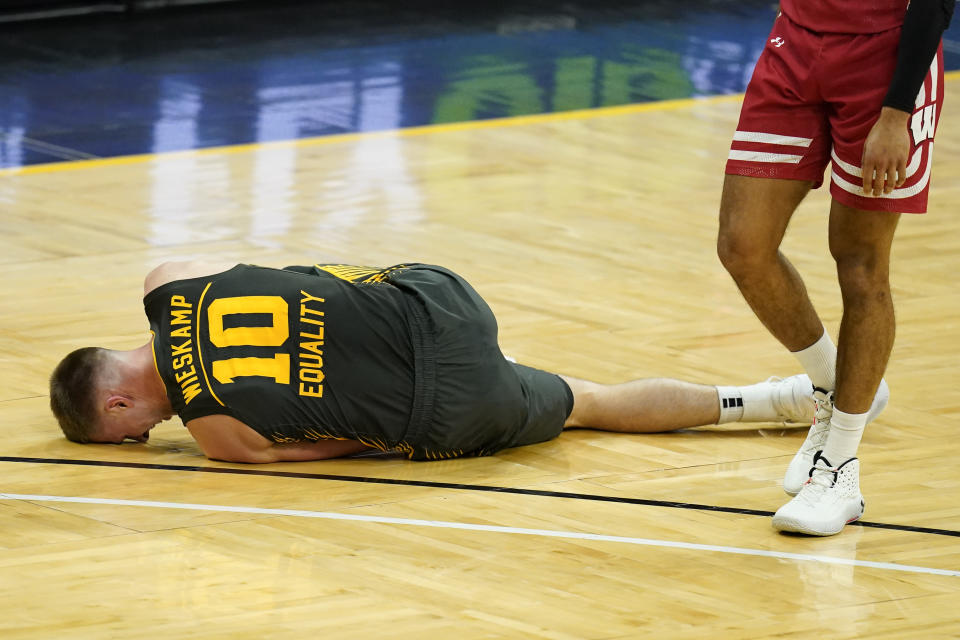Iowa guard Joe Wieskamp rests on the court after getting injured during the first half of an NCAA college basketball game against Wisconsin, Sunday, March 7, 2021, in Iowa City, Iowa. (AP Photo/Charlie Neibergall)