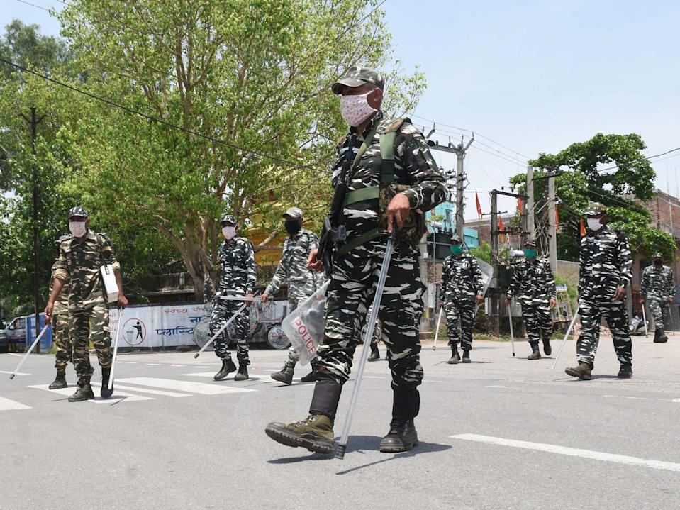 Members of the Central Reserve Police Force patrol a coronavirus containment zone in Ranchi, India, on May 17, 2020.