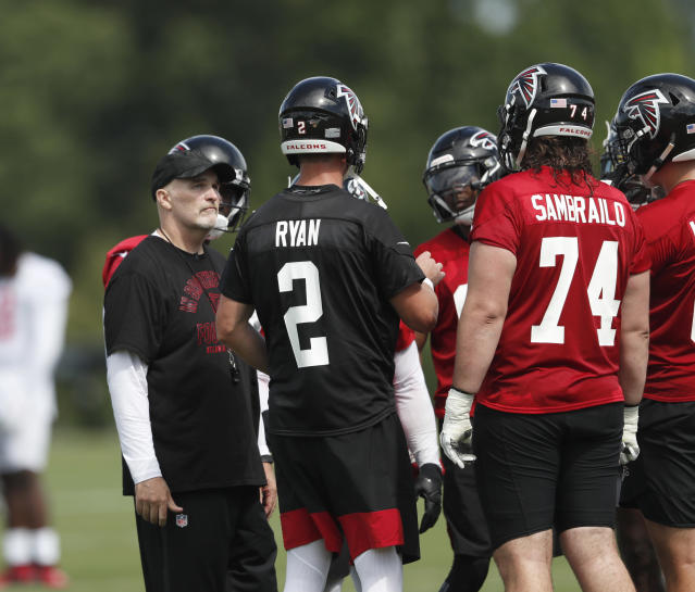 Atlanta Falcons head coach Dan Quinn looks on as quarterback Matt Ryan talks in the huddle during their NFL training camp football practice Monday, July 22, 2019, in Flowery Branch, Ga.(AP Photo/John Bazemore)