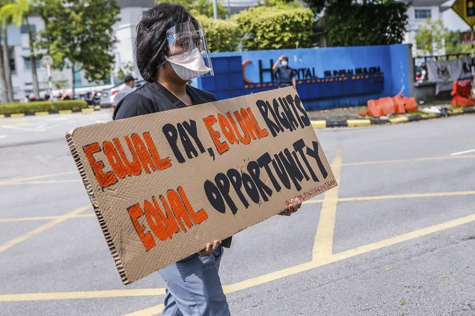 A contract doctor holds aloft a placard demanding equal treatment during a strike at the Sungai Buloh Hospital July 26, 2021. — Picture by Hari Anggara