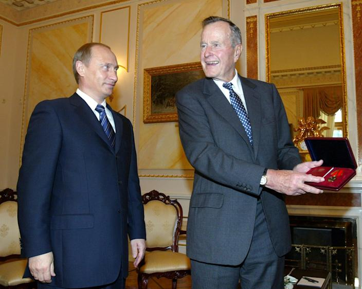 <p>Former U.S. President George H.W. Bush (right) shows a medal on the 60th anniversary of victory in World War II, which he just received from Russian President Vladimir Putin in Moscow on May 23, 2005. (Photo: Sergei Grits/AP) </p>