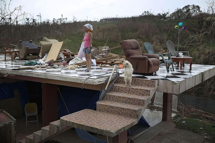 <p>Irma Maldanado and her pets stand in what remains of her home in Corozal, Puerto Rico after Hurricane Maria ravaged the island.</p>