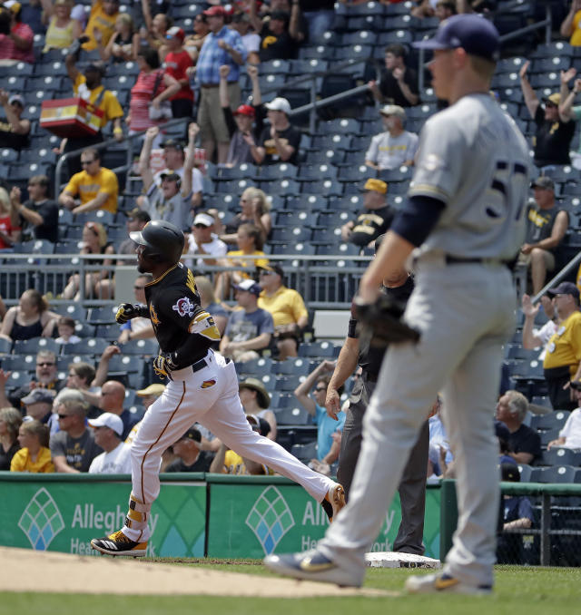 Pittsburgh Pirates' Starling Marte, left, rounds first base after hitting a solo home run off Milwaukee Brewers starting pitcher Chase Anderson (57) in the first inning of a baseball game in Pittsburgh, Saturday, July 14, 2018. (AP Photo/Gene J. Puskar)