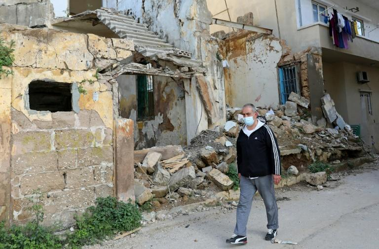 Civil war survivor Jean Saliba, walks past buildings damaged by the August 4, 2020 Beirut port blast, in Karantina district of the Lebanese capital