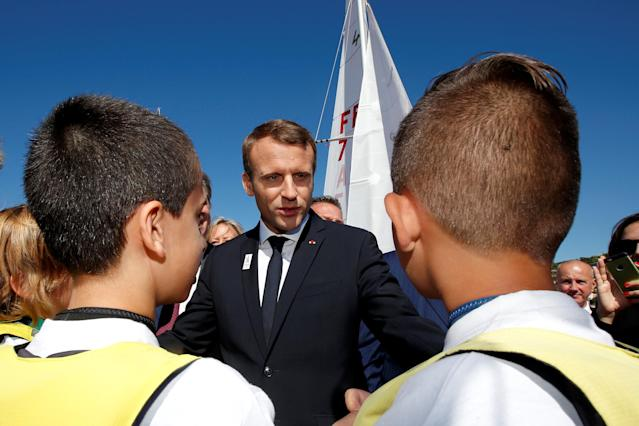 "French President Emmanuel Macron speaks with children as he visits the site of the future Olympic Sailing venue (Voile Olympique) at the ""Marina Olympique"" nautical base in Marseille, France, after the decision for Paris to host of the 2024 Summer Olympics Games, September 21, 2017. REUTERS/Jean-Paul Pelissier"