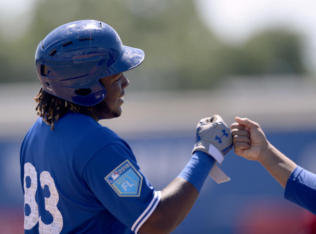 Toronto Blue Jays Dwight Smith Jr. (83) is congratulated after advancing to third on a sacrifice fly during the third inning of a spring training baseball game against the Canada Junior National Team Saturday, March 17, 2018, in Dunedin, Fla. (AP Photo/Jason Behnken)