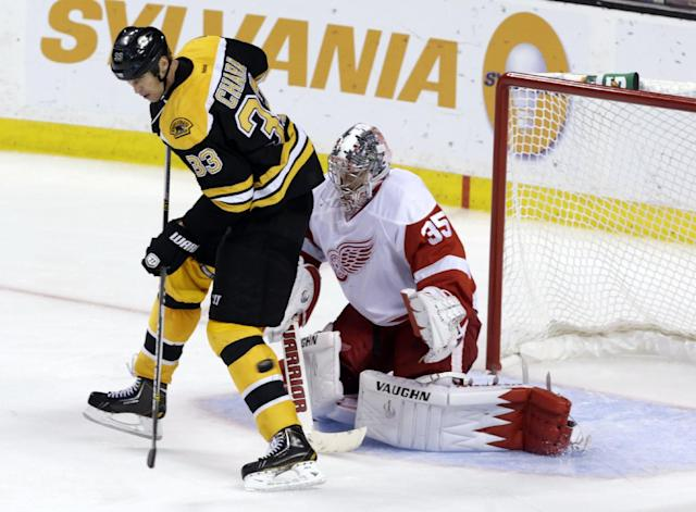 Boston Bruins Zdeno Chara (33) of Slovakia, deflects a shot while screening Detroit Red Wings goalie Jimmy Howard (35)during the third period of an NHL hockey game on Saturday, Oct. 5, 2013, in Boston. (AP Photo/Robert F. Bukaty)