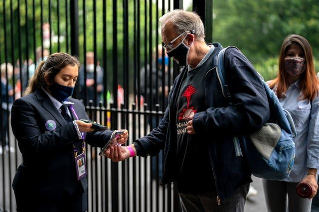 A spectator has a mobile ticket checked at the gate on day one of Wimbledon