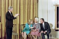 <p>President Bill Clinton and First Lady Hillary Clinton share a light moment with Barbara Bush and former President George H.W. Bush during the unveiling of the Bush formal portraits in the East Room of the White House on July 17, 1995.</p>